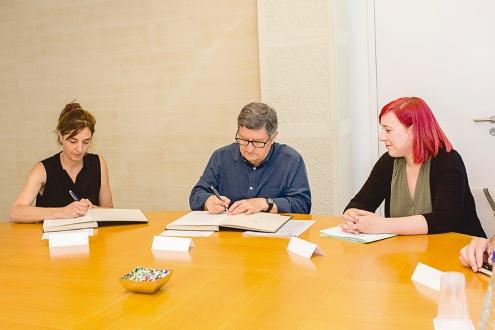 Mireia Barba i Lluís Tejedor signen el conveni, acompanyats per la tinenta d'alcalde de Promoció Econòmica, Comerç i Ocupació, Marta Mayordomo.