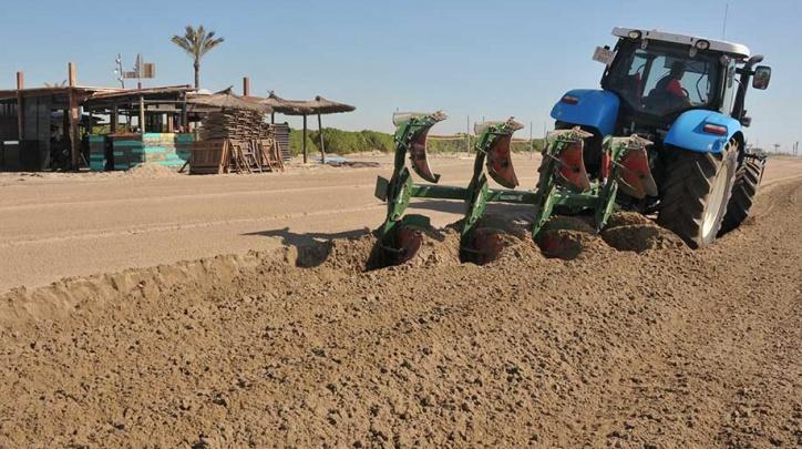 Un tractor llaura la platja del Prat el dimarts 28 de març al matí.