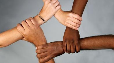 Braços de persones de diferents races units representant el respecte a la diversitat